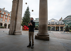 © Licensed to London News Pictures. 23/11/2020. London, UK. A juggler practices in an empty Covent Garden in London as office workers stay away from the City. Prime Minister Boris Johnson will address the Nation tonight to set out his plans for Christmas and the end of lockdown 2.0 with the opening up of shops and restaurants. However he will also introduce a new tougher three-tiered system with further localised restriction to the hospitality industry, Christmas office parties and pub opening hours. Photo credit: Alex Lentati/LNP