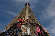 Tourists point out landmarks and admire Paris below from the second level of the Eiffel Tower.