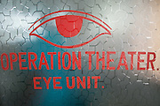 """Bangladesh, Jamuna River, (called the Brahmaputra River in India) near the town of Gaibanda. This is the boat based Friendship non-profit organization (NGO), who provide health care and vocational traing  for locals. Close-up of the words """"Operation Theater Eye Unit,"""" on a glass door."""