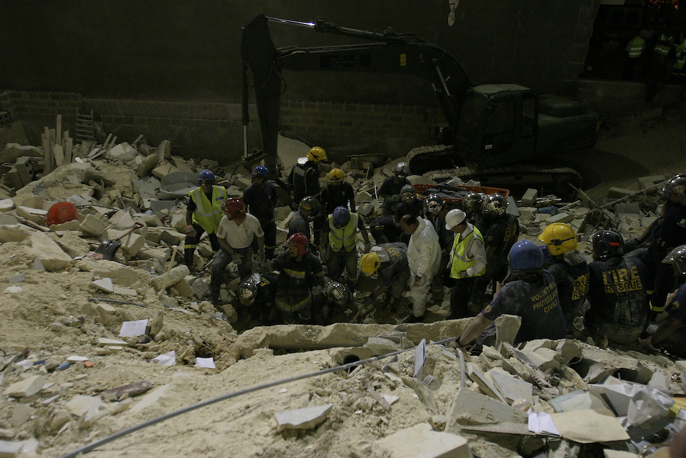 Civil Protection officers and forensic officers examine the lifeless bodies of two women, one Maltese and one Russian, on the site where an apartment block collapsed in the village of St Paul's Bay in the north of Malta early June 4, 2004.   The building collapsed because of excavation works taking place on a site adjacent to it. ..MALTA OUT..REUTERS/Darrin Zammit Lupi