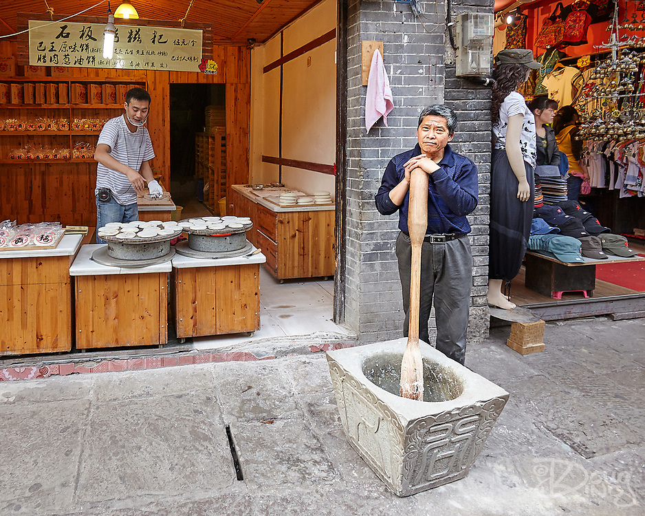 A well dressed elderly man rests on his giant pestle between bouts of effort pounding dough, whilst a younger man in jeans listens to music whilst working in the shop behind.