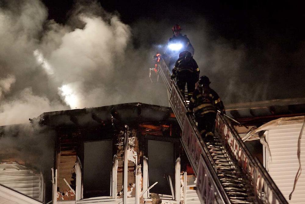 Brockton, MA 01/06/2012.Brockton Fire Department firefighters work at a 2nd alarm fire on Friday night at 10 Johnson Court..Alex Jones / www.alexjonesphoto.com