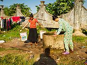 """15 FEBRUARY 2019 - SIHANOUKVILLE, CAMBODIA:  Women collect water from a well in a migrant camp in Sihanoukville. Families who live in the shanty town came to Sihanoukville from other Cambodian provinces because of the town's booming economy and construction industry building Chinese resorts and casinos. There are about 80 Chinese casinos and resort hotels open in Sihanoukville and dozens more under construction. The casinos are changing the city, once a sleepy port on Southeast Asia's """"backpacker trail"""" into a booming city. The change is coming with a cost though. Many Cambodian residents of Sihanoukville  have lost their homes to make way for the casinos and the jobs are going to Chinese workers, brought in to build casinos and work in the casinos.      PHOTO BY JACK KURTZ"""