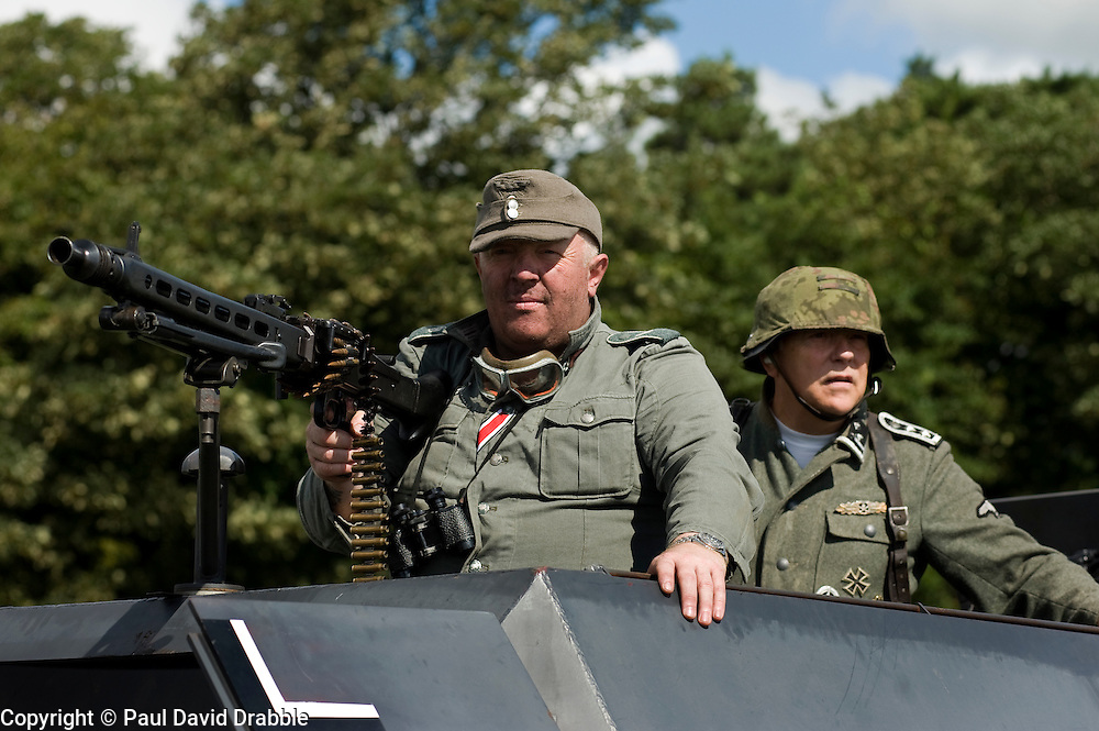 A reenactor portrays a Panzergrenadier from the elite German army GrossDeutschland division with an MG42 (left) while a second reenactor (right) Portrays a member of the SS. Mounted on a Sd.Kfz 251 Auf C Halftrack during a battle reenactment. First Annual Lytham 1940s Weekend held to celebrate the 70th anniversary of the battle of Britain and raise funds for a new Fighter and Bomber Command Memorial to be erected in Lytham. 21 August 2010 Images © Paul David Drabble..