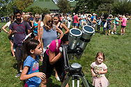 Middletown, New York - People line up on Alumni Green at SUNY Orange to watch a partial solar eclipse through binoculars with solar filters on Aug. 21, 2017.