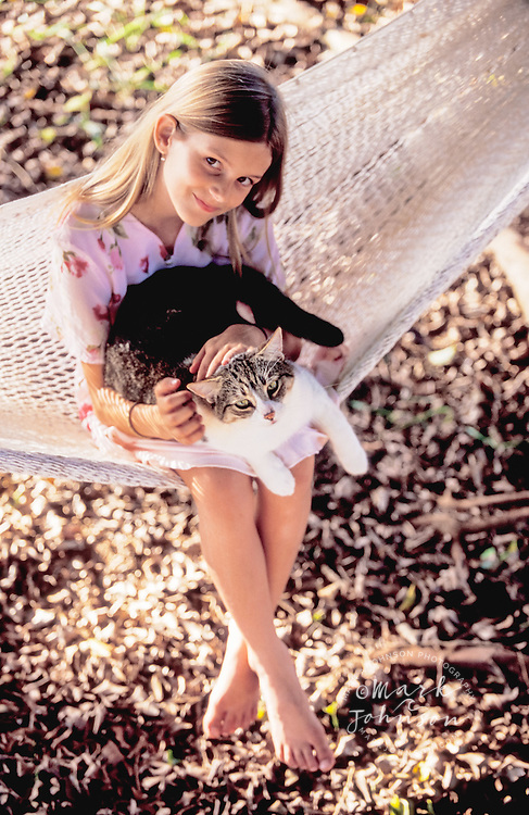 Hawaii, USA --- Girl on a Hammock holding a cat people *****Property Release available ****Model Release available