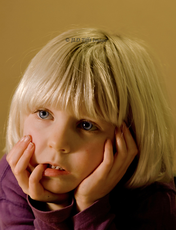 Head shot portrait of a young girl about 5 years old, very blonde, hands to her face, thinking hard.