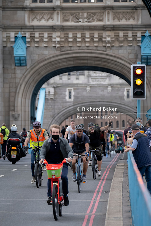After the lifting of both bascules that allowed a tall boat boat to pass underneath, cyclists are the first to cross during the evening rush-hour, on 11th June 2021, in London, England.