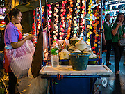 26 MAY 2016 - BANGKOK, THAILAND: A coconut water vendor sets up in the Silom Road night market. The night market on Silom Road, close to Bangkok's famous Patpong tourist area, is being closed by the Bangkok municipal government. Vendors have been told they have to leave the sidewalk on Silom Road by the end of May, 2016. The market is the latest street market being shut down by city officials as a part of the government's plan to clean up Bangkok. The Silom Road night market sells mostly tourist oriented clothes, inexpensive Thai art, and bootleg movies on DVD.       PHOTO BY JACK KURTZ