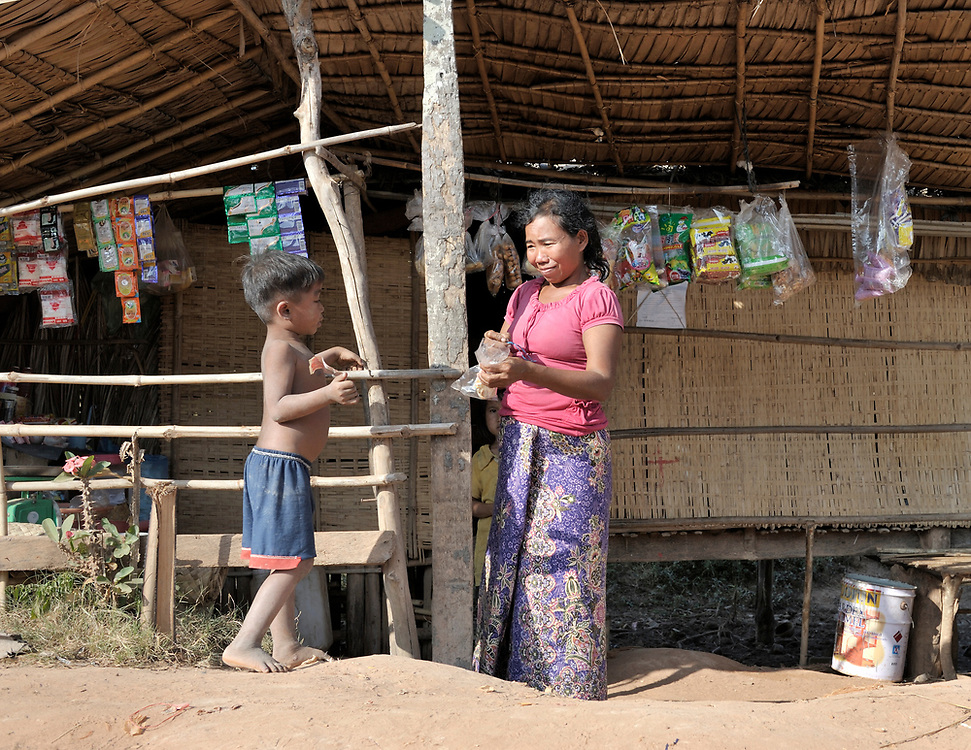 Neak Toy, selling merchandise in front of her home and store in Svay Phaerm, a village in the Kampot region of Cambodia.