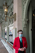 During the UKs Coronavirus pandemic lockdown and in the 24hrs when a further 255 deaths occurred, bringing the official covid deaths to 37,048, <br /> an employee Fortnum & Mason wearing a face mask and face shield stands outside the famous department store on Piccadilly, in preparation for the re-opening of their Food Hall on June 15th, as per governmental guidelines, on 26th May 2020, in London, England.