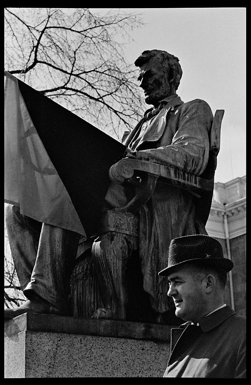 Madison, WI - March 1970. A man stands near the statue of Abraham Lincoln in front of Bascom Hall, tbe statue with a black and red anarcho-syndicalism flag. On March 15, 1970, the University of Wisconsin - Madison Teaching Assistants' Association voted to strike, and the campus was filled with picket lines as well as demonstrations of related and other issues. The strike lasted until early April, when the Association and University came to an agreement.
