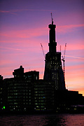 Silhouette of The Shard under construction against a pink and purple sky and clouds at sunset. Night scene of The Shard, the latest tall building to be built in London under construction at London Bridge. This is a controversial project as this will be a true sckscraper at some 70 plus stories tall. At 310m this will be London's talles building by far. Due for completion in early 2012.