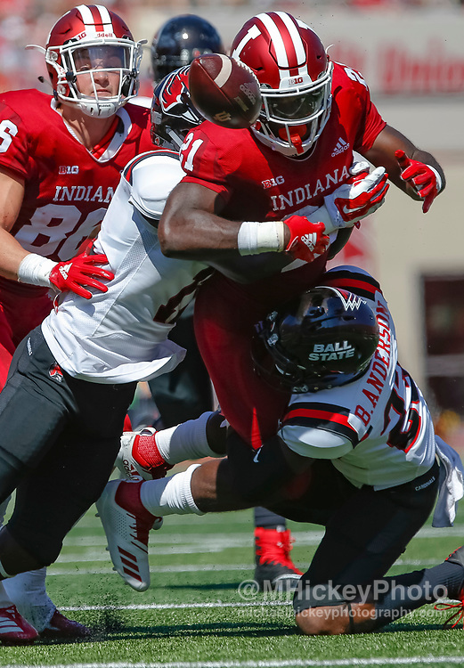 BLOOMINGTON, IN - SEPTEMBER 15: Stevie Scott #21 of the Indiana Hoosiers fumbles the ball as Ray Wilborn #11 and Brett Anderson II #23 of the Ball State Cardinals make the stop at Memorial Stadium on September 15, 2018 in Bloomington, Indiana. (Photo by Michael Hickey/Getty Images) *** Local Caption *** Stevie Scott; Ray Wilborn; Brett Anderson II NCAA Football -  Indiana Hoosiers vs Ball State Cardinals at Memorial Stadium in Bloomington, Indiana. Sports photography by Michael Hickey