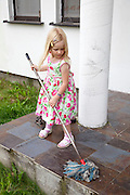 Young polish girl age 4 in flowered dress mopping front porch of her home. Zawady Central Poland