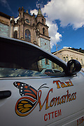 A taxi parked in Angangueo, Mexico in the center of the Monarch Butterfly Biosphere Reserves in central Mexico in Michoacan State. The town celebrates the Monarch Butterflies which attract tourists from around the world. Each year hundreds of millions Monarch butterflies mass migrate from the U.S. and Canada to Oyamel fir forests in the volcanic highlands of central Mexico. North American monarchs are the only butterflies that make such a massive journey—up to 3,000 miles (4,828 kilometers).