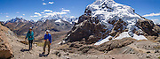 """Trekkers reach Punta Cuyoc (16,200 feet or 4950 m pass), beneath Nevados Puscanturpa. Day 5 of 9 days trekking around the Cordillera Huayhuash in the Andes Mountains, Peru, South America. In the distance, see Siula Grande (center left 20,814 ft or 6344 m), which was the subject of the gripping 2003 British docudrama """"Touching the Void."""" In 1985, climbers Joe Simpson and Simon Yates scaled the treacherous West Face of Siula Grande, but after Joe broke his leg, their descent became one of the most amazing survival stories in mountaineering history. The 2003 movie is based upon Joe Simpson's harrowing book, """"Touching the Void: The True Story of One Man's Miraculous Survival."""" Day 5 of 9 days trekking around the Cordillera Huayhuash in the Andes Mountains, Peru, South America. This panorama was stitched from 4 overlapping photos. For licensing options, please inquire."""
