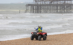 Licensed to London News Pictures. 04/05/2021. Brighton, UK. Environmental officers patrol the beach at Brighton, East Sussex as high winds continue to batter the UK this morning. Today, the Met Office have issued weather warnings across the South of England for stormy weather with winds speeds expected to reach up to 50mph again. However forecasters predict the high winds to ease this week but with wind and rain coming back for the weekend. Photo credit: Alex Lentati/LNP