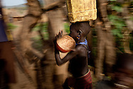 A girl runs home with water in a town near Boma.