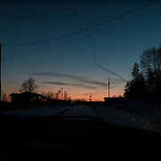 Sunset over the main road into the Ochiichagwe'Babigo'Ining Ojibway Nation reserve (also known as the Dalles First Nation) in Northern Ontario, Canada as seen through a car windscreen on 18 December 2016.