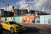Yellow Chevrolet Camaro car passing the redevelopment of Battersea Power Station and its surroundings on 1st February 2020 in London, England, United Kingdom. Battersea Power Station is a decommissioned coal-fired power station located on the south bank of the River Thames, in Nine Elms, Battersea, an inner-city district of South West London. Now a well advanced construction site and under development, the site will become both residential and commercial property.