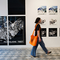 """VENICE, ITALY - JUNE 04:  A woman walks in front of prints at  """"The Pavillion Tibet"""" a project by Ruggero Maggi on June 4, 2011 in Venice, Italy. The Venice Art Biennale will run from June 4 to November 27, 2011."""