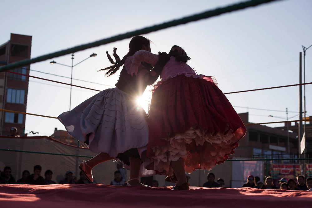 """Como parte del espectáculo """"Cholitas Wrestling""""  dos cholitas luchadoras se enfrentan sobre un tarima acondicionada como ring de box en las calles de la feria 16 de julio de la gran ciudad de El Alto, La Paz, Bolivia."""
