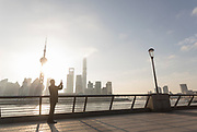 View of futuristic architecture of the Pudong skyline and a male tourist taking pictures, The Bund, Shanghai, China