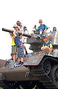 Kids ages 7 through 11 playing on immobilized tank in park.  WestPlatte Poland