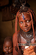 Viahondjera Musutua, a Himba woman who lives in the small village of Ondjete in northwestern Namibia , sits inside her home with her child. (Viahondjera Musutua is featured in the book What I Eat: Around the World in 80 Diets.)