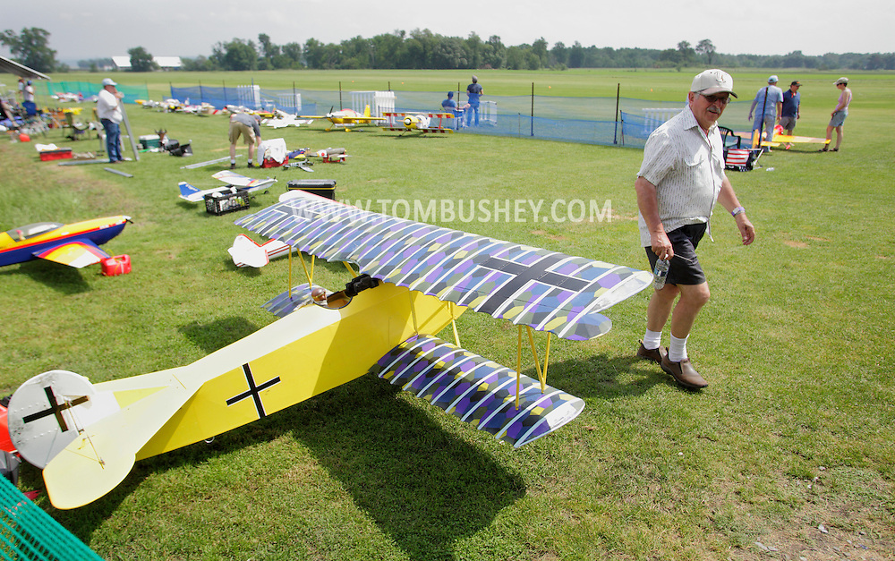 New Hampton, New York - A man walks past a remote controlled biplane at a fly-in sponsored by the Wawayanda Flying Club at  on June 5, 2010.
