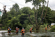 Police officers from Hampshire Police Marine Support Unit and Thames Valley Police monitor Swan, an environmental activist from HS2 Rebellion sitting on a line above the river Colne seeking to protect an ancient alder tree on the far bank from destruction, as tree surgeons working with the National Eviction Team continue to cut the tree during works for the HS2 high-speed rail link on 24th July 2020 in Denham, United Kingdom. Officers from the Metropolitan Police, Thames Valley Police, City of London Police and Hampshire Police attended to ensure the removal of the tree by HS2 despite protests from activists.