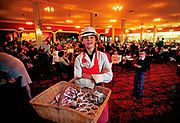 Boy selling seafood in the bar at Butlins holiday camp, Skegness. Butlins Skegness is a holiday camp located in Ingoldmells near Skegness in Lincolnshire. Sir William Butlin conceived of its creation based on his experiences at a Canadian summer camp in his youth and by observation of the actions of other holiday accommodation providers, both in seaside resort lodging houses and in earlier smaller holiday campsThe camp began opened in 1936, when it quickly proved to be a success with a need for expansion. The camp included dining and recreation facilities, such as dance halls and sports fields. Over the past 75 years the camp has seen continuous use and development, in the mid-1980s and again in the late 1990s being subject to substantial investment and redevelopment. In the late 1990s the site was re-branded as a holiday resort, and remains open today as one of three remaining Butlins resorts.