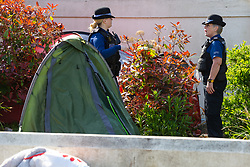 Police community Support Officers patrolling Worthing investigate tents pitched on council-owned grounds surrounding Beach House in Worthing, West Sussex, where homeless campers have been camping. Worthing, West Sussex, April 30 2019.