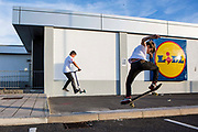 Wadebridge youngsters skating and scootering in Lidl car park. WREN community energy has given funding received from the Feed in tariff from their solar array to a project that build a local skate park within the town. Wadebridge, Cornwall. UK