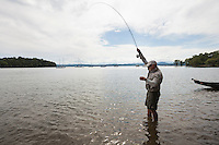 Angler and guide Drew Price plays a carp on the fly, lake champlain