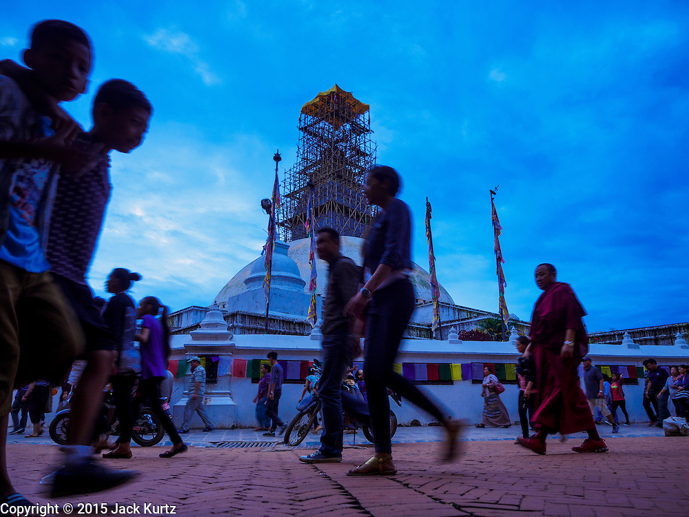 31 JULY 2015 - KATHMANDU, NEPAL: People walk around Bodhnath Stupa during the full moon procession. Bodhnath Stupa in the Bouda section of Kathmandu is one of the most revered and oldest Buddhist stupas in Nepal. The area has emerged as the center of the Tibetan refugee community in Kathmandu. On full moon nights thousands of Nepali and Tibetan Buddhists come to the stupa and participate in processions around the stupa. The stupa was heavily damaged in the earthquake of 25 April 2015 and people are no longer allowed to climb on the stupa, now they walk around the base and pray with butter lamps.   PHOTO BY JACK KURTZ