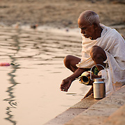 Elderly bather performing ablution in the Ganges early in the morning at one of the ghats.