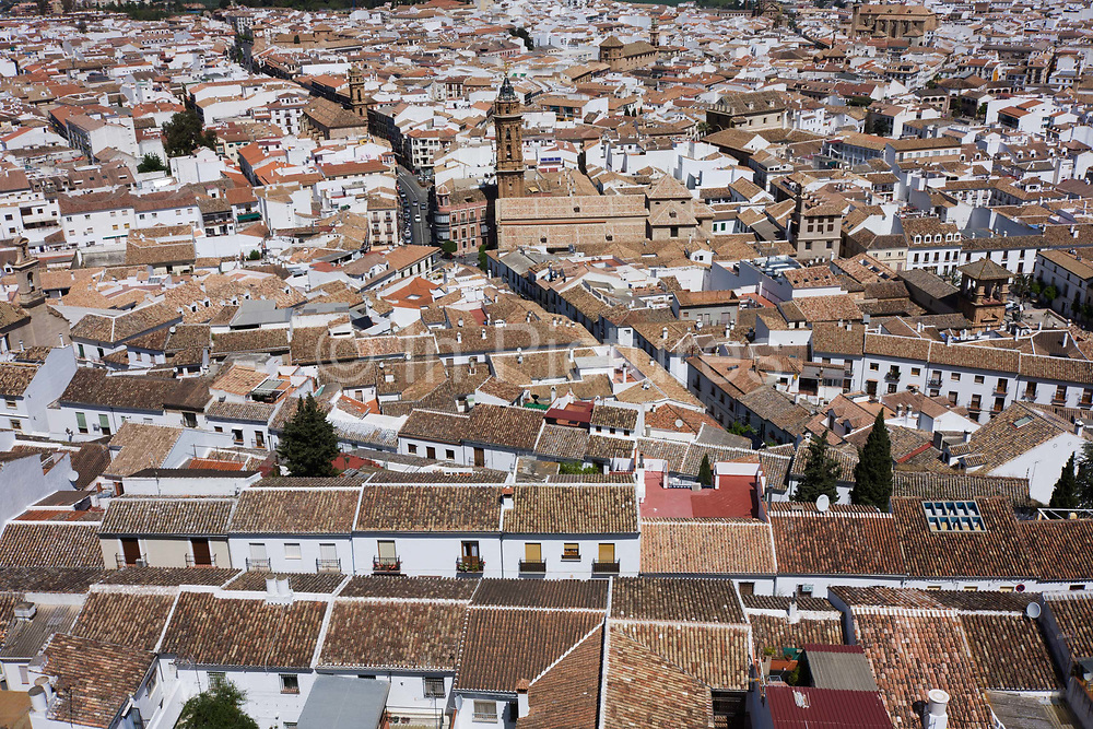 """Rooftops of the church of San Sebastian, in Antequera, Andalucia. From the hilltop castle that overlooks the city, we see the Spanish streets, homes and businesses. Antequera is a city and municipality in the province of Málaga, part of the Spanish autonomous community of Andalusia. It is known as """"the heart of Andalusia"""" (el corazón de Andalucía) because of its central location among Málaga, Granada, Córdoba, and Seville. In the last quarter of the 1st millennium BCE, the Iberian peninsula became part of the Roman Empire but  the year 711 a tribe of Berbers out of North Africa (Moors) invaded Spain and conquered Antikaria around 176, renaming it Medina Antaquira."""