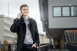 Teenage businessman waiting for someone and talking on cellphone and smiling, Bavaria, Germany