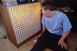 Teenage boy with Downs Syndrome sitting on floor looking at disco lights,