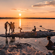 Cucuí, Amazonia. Triple border Brazil, Colombia and Venezuela. A family swimming and taking bath at sunset. In front of them, on the other side of the Negro river is the Colombian territory and the cocaine fields controlled by the FARC army (Fuerzas Armadas Revolucionarias de Colombia)