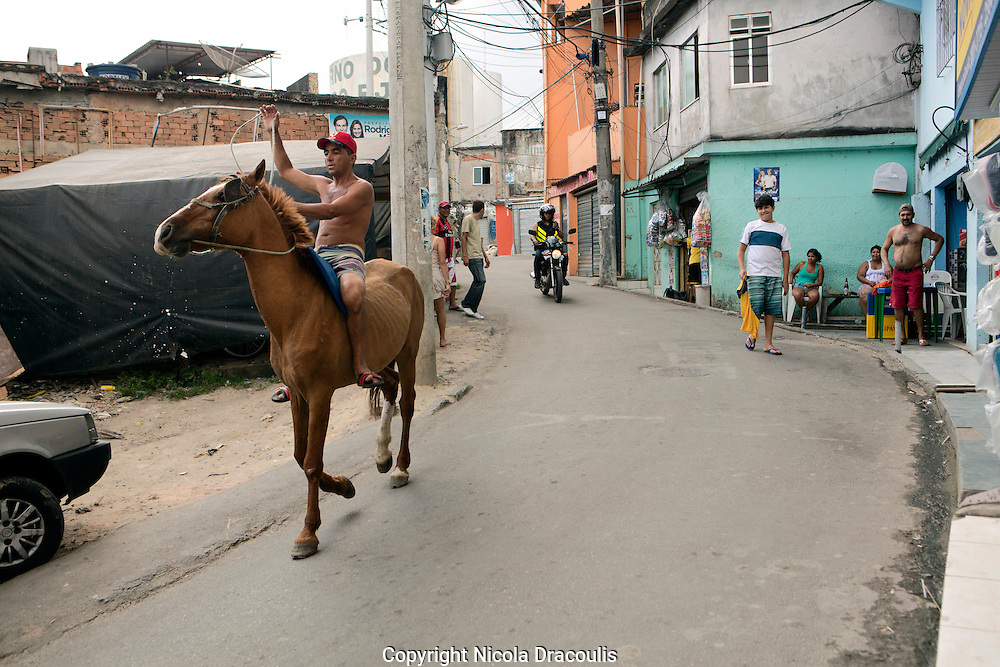 Man riding horse through, Complexo do Alemão 2013 <br /> Part of the series Viver no Meio do Barulho (Living in the Middle of the Noise).