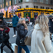 Shoppers and visitors walk down 5th Avenue for the Holiday season during the Coronavirus (Covid-19) outbreak in Manhattan,New York on Sunday, December 6, 2020. (Alex Menendez via AP)