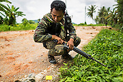 08 JULY 2013 - MAYO, PATTANI, THAILAND:  A Thai soldier pauses on the side of a road in Pattani province after a truck carrying eight of his colleagues was destroyed by an IED Monday. Eight Thai soldiers were injured - one seriouly and seven with minor injuries - when their truck was hit by an IED outside Mayo, Pattani province in southern Thailand Monday. The soldiers were returning from a teacher protection mission when their truck ran over the explosive. The attack was thought to be conducted by Muslim insurgents who have been battling the Thai government for greater autonomy. The conflict in southern Thailand has claimed about 5,000 lives since 2004.   PHOTO BY JACK KURTZ