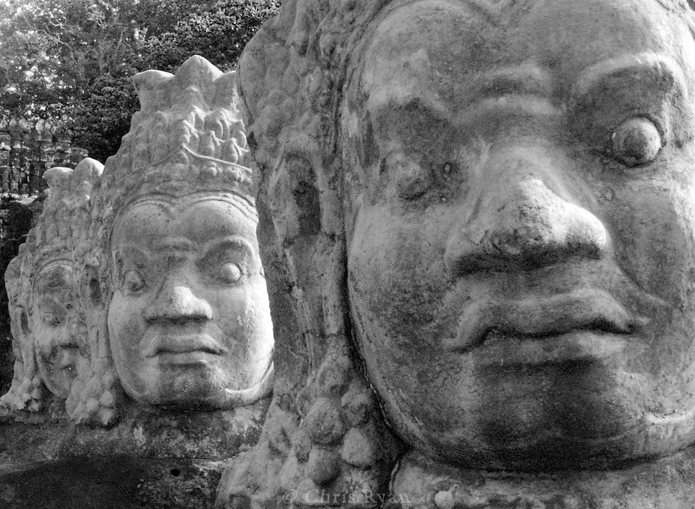Stone-carved heads lining the entrance bridge at Bayon temple, Angkor, Cambodia