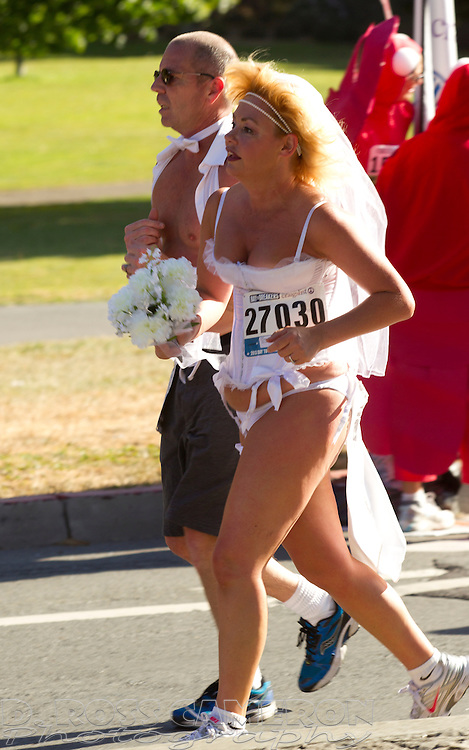 A bride and groom in lingerie jog through Golden Gate Park during the 102nd running of the Bay to Breakers 12K in San Francisco, Sunday, May 19, 2013. More than 30,000 runners -- from the elite to the weekend warrior -- made the 7.62-mile trek from Howard and Spear to the Great Highway. (Photo by D. Ross Cameron)