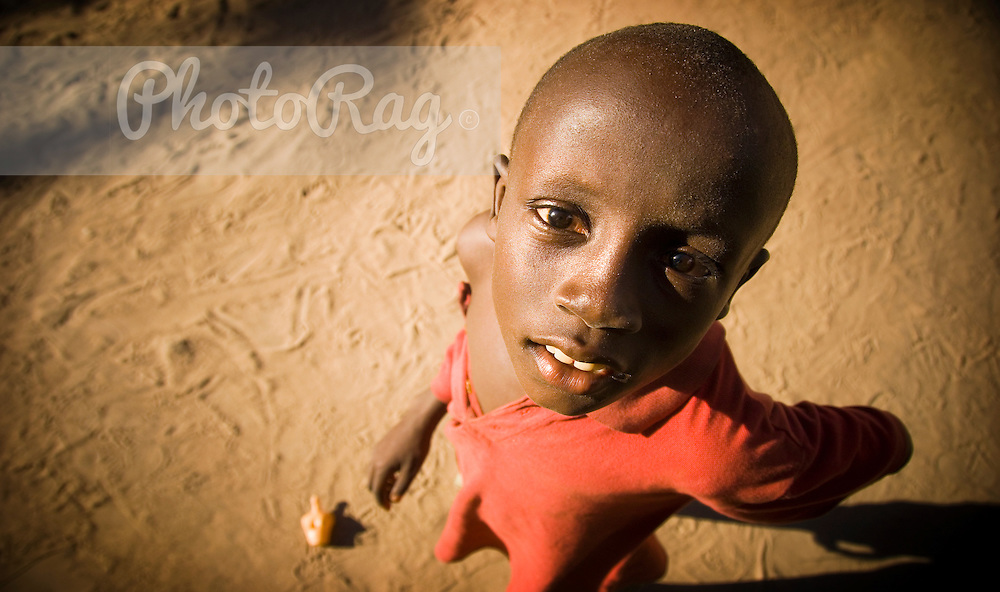 A young boy looks up straight to the camera, after playing with his friends on the sandy path of Boboi Beach village in Gambia, Africa. No other continent comes close to it for scale, variety and pure, raw impact. Africa offers a travel experience a hundreds of miles from the well-backpacked, air-conditioned tourist trails of Southeast Asia or the cash-cow adventure parks of USA or Australia. But Gambia is easy to miss on a map of mighty Africa. This tiny sliver of land is a mere 50km wide and 500km long, and, with the exception of an 80km shoreline, it's entirely enveloped by the much more talked about and supposedly 'colourful' Senegal. But, since when has a 'real experience' been about following the crowd along their 'beaten track' ..Those that do make it to Gambia often come home with fantastic tales from the depths of the River Gambia or one of the countries superb national parks. From the first rays of sunlight, visitors will boast about the symphony of baboon barks, bird calls and the playful shrieks of the endless chimps but personally, I think the real 'heart of Gambia' lies in the country's vibrant culture and the incredibly warm and open locals. Yes of course there is the chance to laze and linger in anything from a luxurious beach resort to a deserted bay just outside a bustling fishing village but if you're in search of atmosphere and memories of thought provoking encounters, then forget where you come from for a minute and let the friendly youth of Gambia show you there lives, their homes and their hearts. ..Being a relatively poor Western African country, Gambia is not without its social & environmental issues. Political instability & corruption, poverty and severe littering are all common problems throughout the country but after an afternoon spent in one of the many dusty seaside villages, one learns that the Gambians are far prouder of their colourful identity and their passion for football, music and art and if you take the chance to open your eye