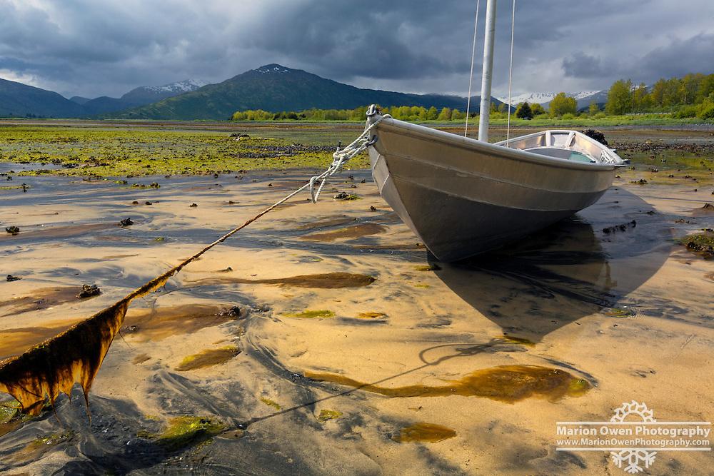 Aluminum skiff settles in sand at low tide in Womens' Bay, Kodiak, Alaska