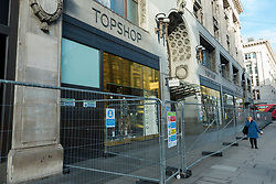 © Licensed to London News Pictures. 28/01/2021. LONDON, UK. Construction fencing surrounds Topshop's flagship on Oxford Street, the traditional home of retail in the West End. Online retailer Asos is reported to be interested in buying the parts of the business from owner Arcadia which recently collapsed into administration.  Already suffering from competition from online shopping, the coronavirus pandemic has resulted in reduced footfall and lockdowns have forced non-essential shops to close.  Photo credit: Stephen Chung/LNP